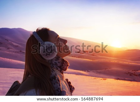 Image of pretty woman walking in snowy mountains, side view of cute girl looking up, closeup portrait of female wearing warm winter earmuff, red sunset, wintertime sports, trekking and hiking concept - stock photo