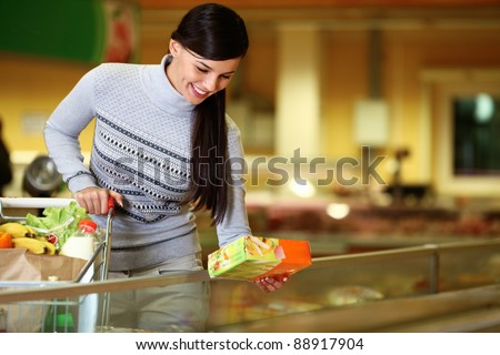 Image of pretty woman with cart choosing products in supermarket - stock photo