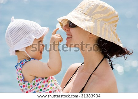 Image of pretty woman with her little baby on blue background - stock photo