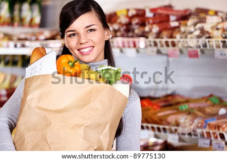 Image of pretty woman with pack of products looking at camera - stock photo