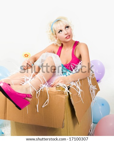 Image of pretty young girl sitting inside box and holding lollypop while looking upwards