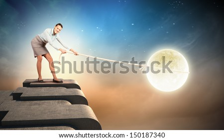 Image of pretty young woman pulling moon - stock photo