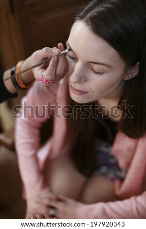 image of production make up, beautiful brunette girl is having a production of her make up, film production, actress , Portrait of a Beautiful woman with makeup brush near her face