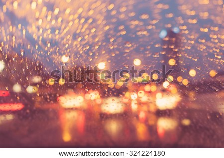 Image of raindrops on a car window at night in the city, Street Bokeh Lights defocused, with retro filter effect. - stock photo