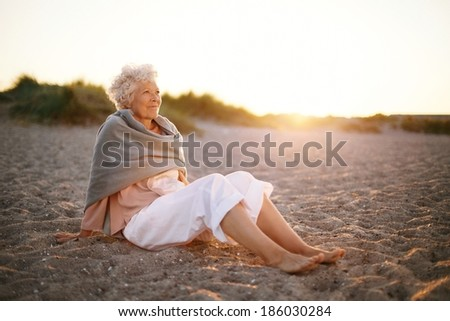 Image of relaxed elderly woman sitting on the beach looking at a view. Senior woman wearing shawl sitting on beach. - stock photo