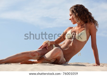 Image of relaxing woman lying on the sand - stock photo