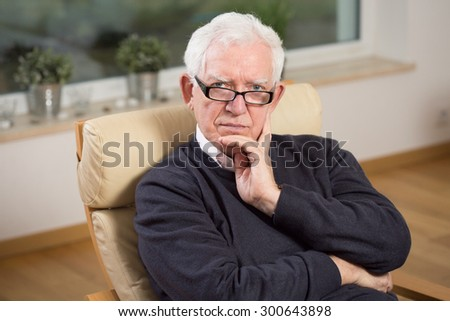 Image of retired man sitting on the chair - stock photo
