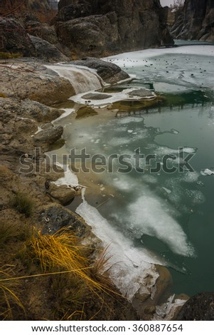 Image of river with green waters, snow and ice near Meteora in Greece