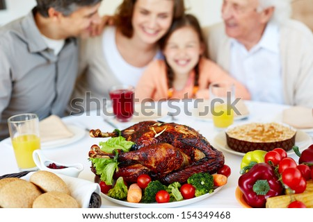 Image of roasted turkey on holiday table and family on background - stock photo