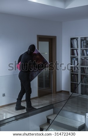 Image of robber stealing picture at night - stock photo