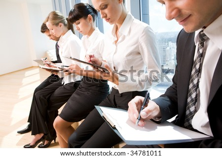Image of row of business people writing on papers at seminar