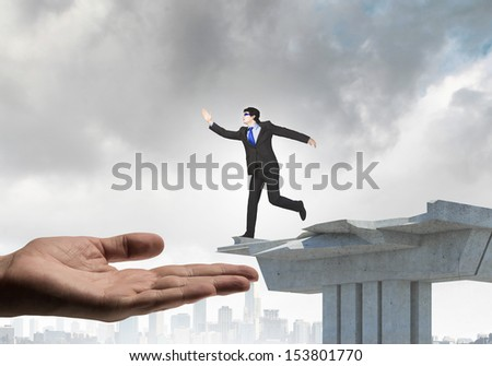 Image of running businessman at the edge of bridge supported by human hand - stock photo