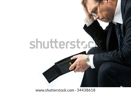 Image of sad businessman holding empty wallet and grieving - stock photo