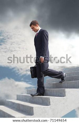 Image of sad businessman walking downstairs - stock photo