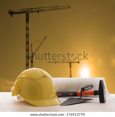 image of safety yellow helmet and architect paper plant on white table with sun set scene and building silhouette crane construction on background  - stock photo