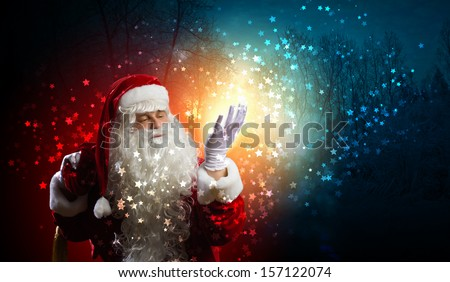 Image of Santa Claus in red costume against dark background - stock photo