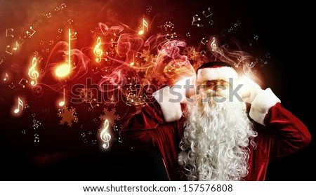 Image of Santa Claus in red costume wearing earphones - stock photo