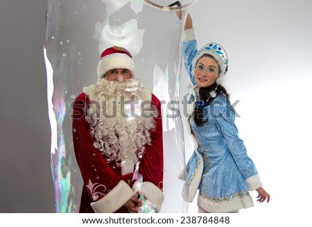 Image of Santa Claus in soap bubble and snow girl