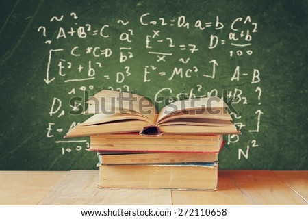 image of school books on wooden desk over green background with formulas. education concept - stock photo