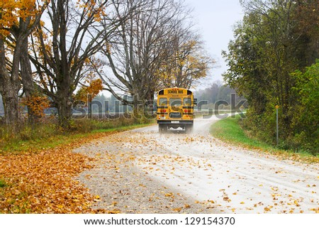 Image of school bus is taking the road that full of autumn trees with dried leaves - stock photo