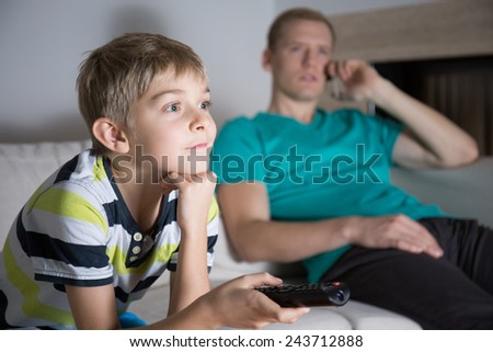 Image of schoolboy addicted to watching tv - stock photo