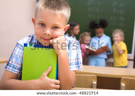 Image of schoolboy looking at camera on background of classmates - stock photo