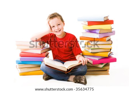Image of schoolboy sitting between two heaps of books and reading one of them - stock photo