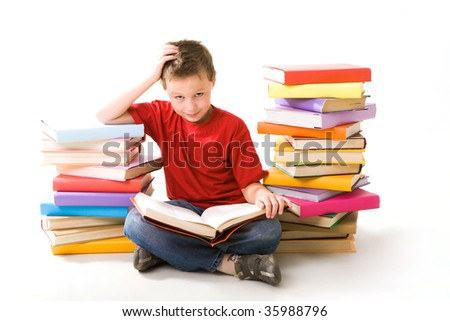 Image of schoolboy sitting between two heaps of books and reading one of them