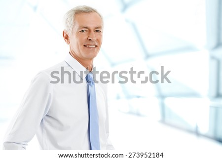 Image of senior broker standing at office while looking at camera and smiling. Business people. - stock photo