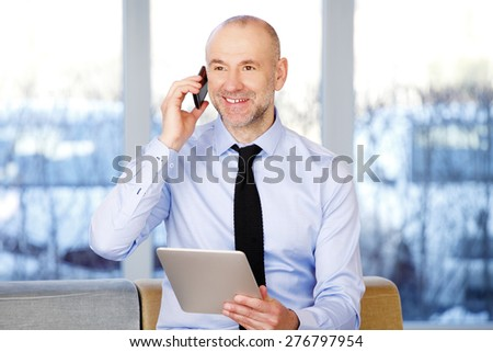 Image of senior businessman sitting at office and making call while holding digital tablet in his hands.  - stock photo