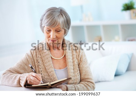 Image of senior female making notes in notepad