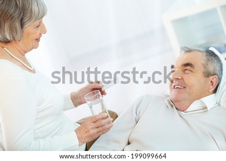 Image of senior female offering her sick husband to take pill - stock photo
