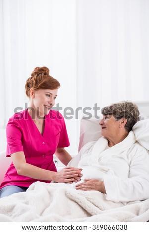 Image of senior lady with nurse on geriatric ward - stock photo