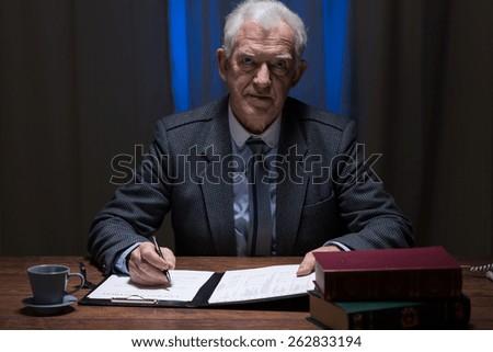 Image of senior lawyer working at night - stock photo