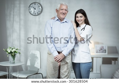 Image of senior man and caring doctor - stock photo