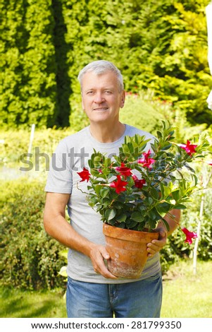Image of senior man standing at garden at home while holding hands pot of flower.