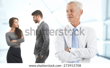 Image of senior sales man standing at office with arms crossed while businesswoman and businessman standing at background.