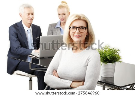 Image of senior smiling businesswoman standing with arms crossed while business people working at background with laptop.   - stock photo