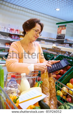 Image of senior woman hand touching buttons of calculator with goods in cart near by - stock photo