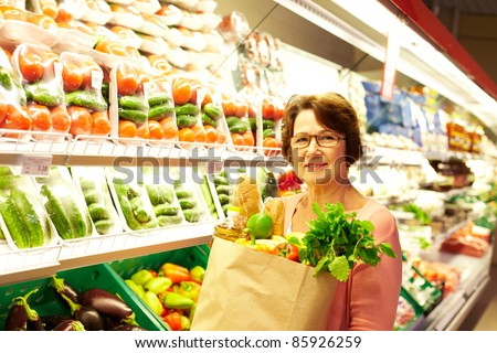 Image of senior woman in groceries department - stock photo