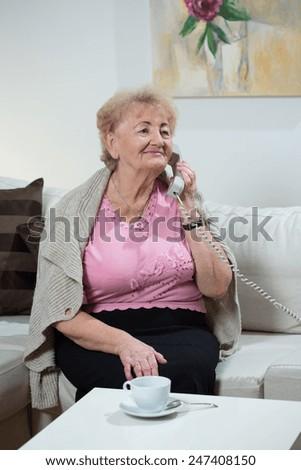 Image of senior woman talking on landline phone - stock photo