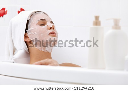 Image of serene woman with facial mask enjoying bath in spa salon - stock photo