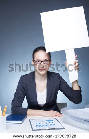 Image of serious businesswoman with blank paper in her hand looking at camera - stock photo