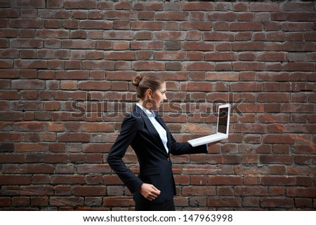 Image of serious businesswoman with laptop walking along brick wall - stock photo