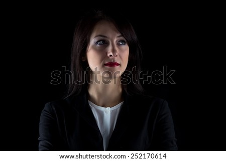 Image of serious looking away brunette business woman on black background