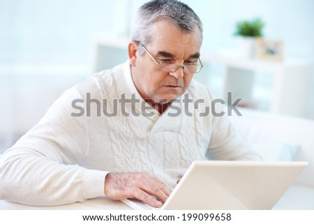 Image of serious pensioner using laptop at home - stock photo