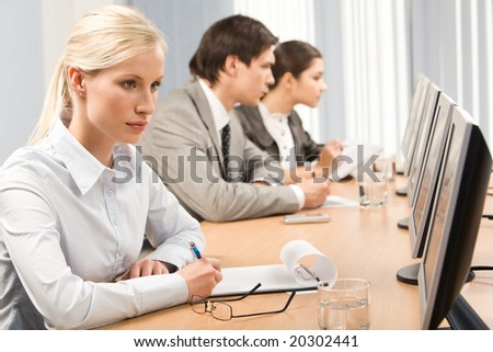 Image of serious woman sitting at workplace and looking at monitor of computer