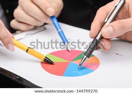 Image of several hands over business charts - stock photo