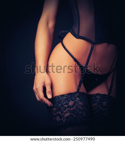 Image of sexy woman in black underwear and stockings. Black background. - stock photo