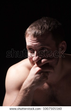 Image of shirtless man keeping his hand by face, black background